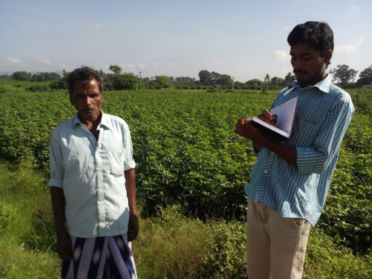 Youth volunteer taking notes from farmer-Oct 2015