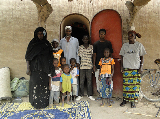 Family in Dendjola in front of their NV house