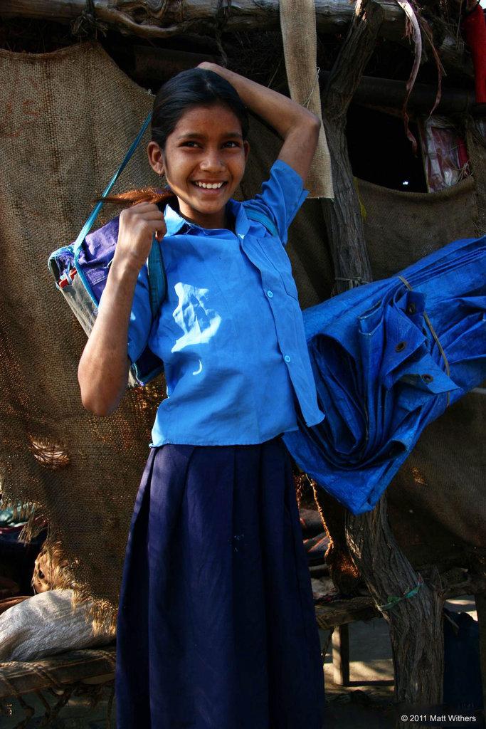 A happy girl packs her schoolbag