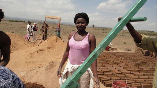 Worker and bricks, sieve in background