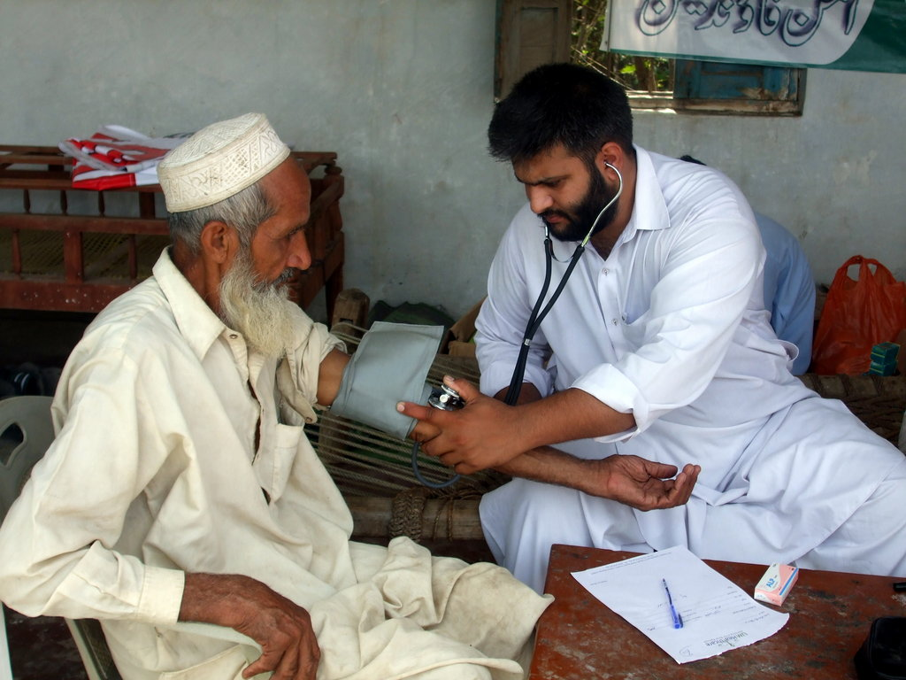Dr.Haider from UM Healthcare Trust is treating an old patient during the free medical camp in flood effected area of Pakistan. The medical services are provided in resource challenged areas.