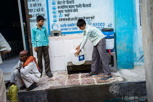 Two boys filling up their iJal with safe water