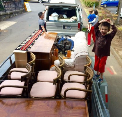 Happy kid helping pack his family's furniture