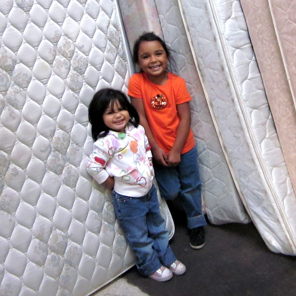 Two sisters giggle, side-by-side, in front of their brand new mattresses from Community Warehouse. These will accompany a basket full of colorful linens, pillows, and blankets in the car, ready to be made into cozy beds as soon as they get home.