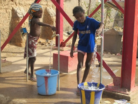 Village children try out the new well's pumps.