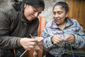Silvia asks Rosa for guidance while knitting.