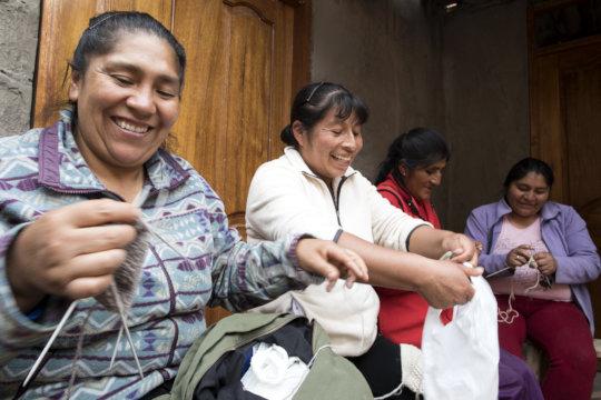 Rosa, Matilda, Demi and Yudi laugh while knitting.