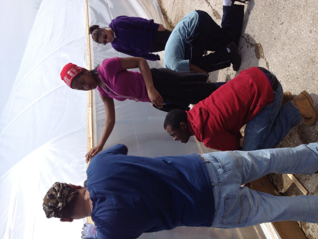 Teens helping construct the new compost hoop house