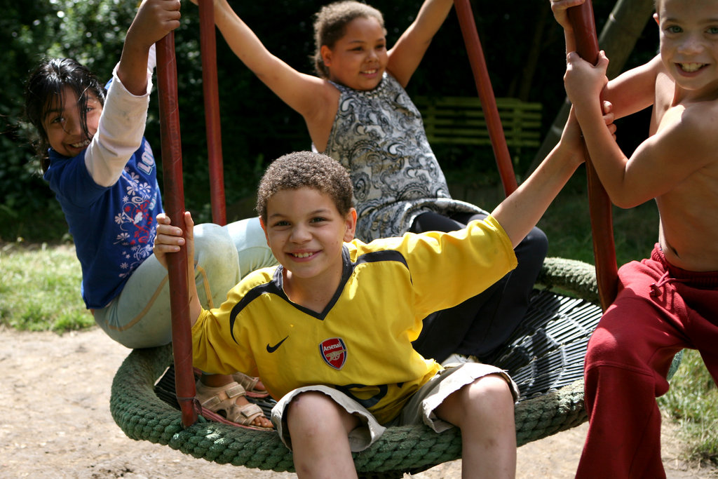 Four children playing in KIDS summer playsheme at KIDS Hayward Adventure Playground in Islington, London. This allows parents to take a short break while their children are out of school.