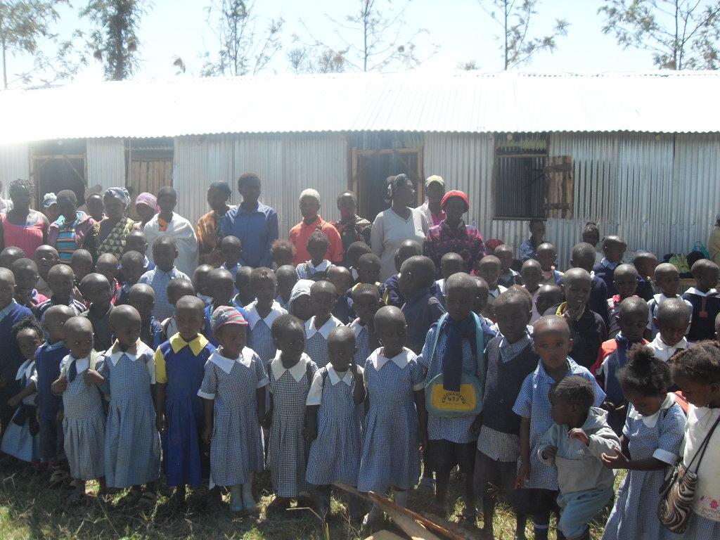 Children and teachers in front of new school