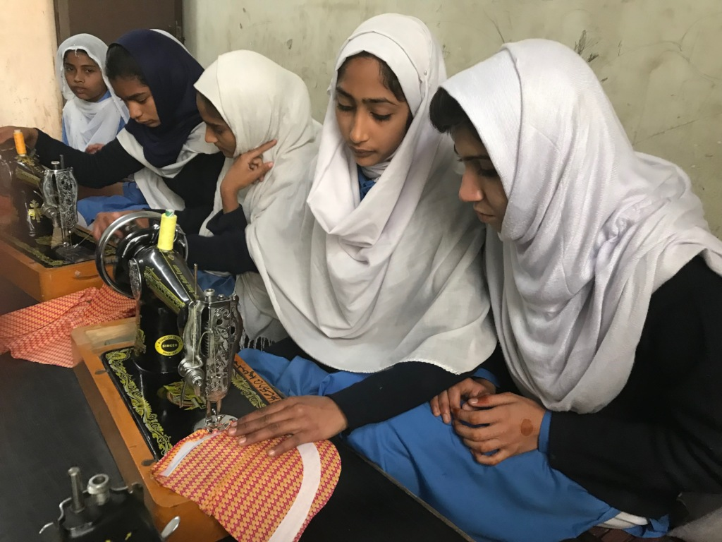 Girls stitching a shirt in the new sewing room
