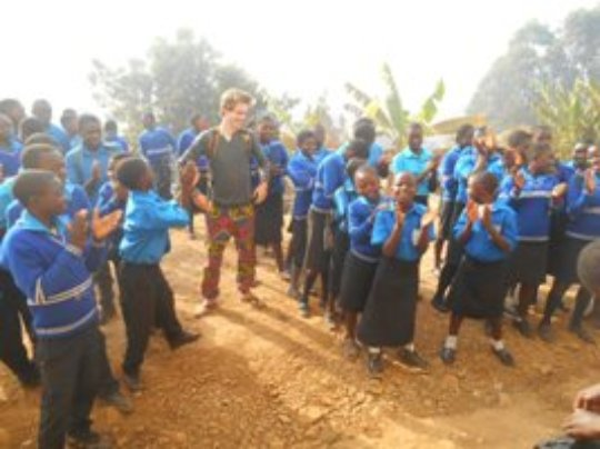 students and  volunteer HENRICK  at the assembly