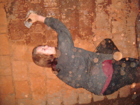 Nancy a volounteer  plastering the wall seriously