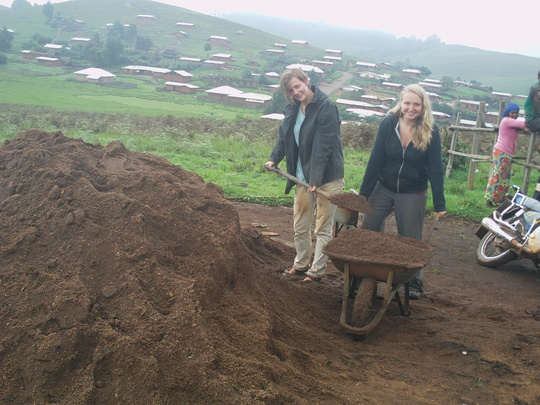 Volunteers carrying sand for the plastering