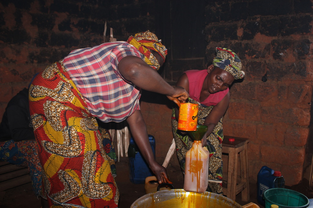 Women heating the Palm oil in order to share