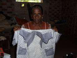 Mrs. Kanmani sews men's shirts to sell at market