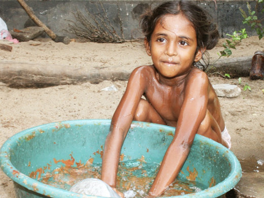 A little Sri Lankan foster girl doing her normal chores in her daily life.