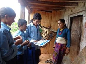 students using flip-chart to educate a villager