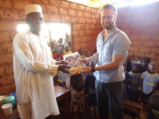 Volunteer handing gift to the School Head teacher