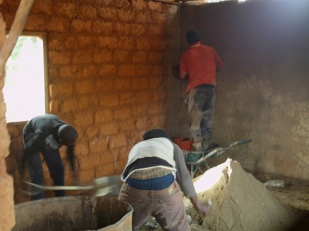 THE BRICKLAYER IS BUSY PLASTERING THE WALL