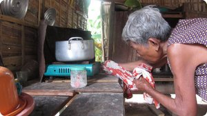 Her mother tinkers with the biogas-cooked lunch.
