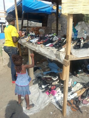 Loan recipient at her used shoes store