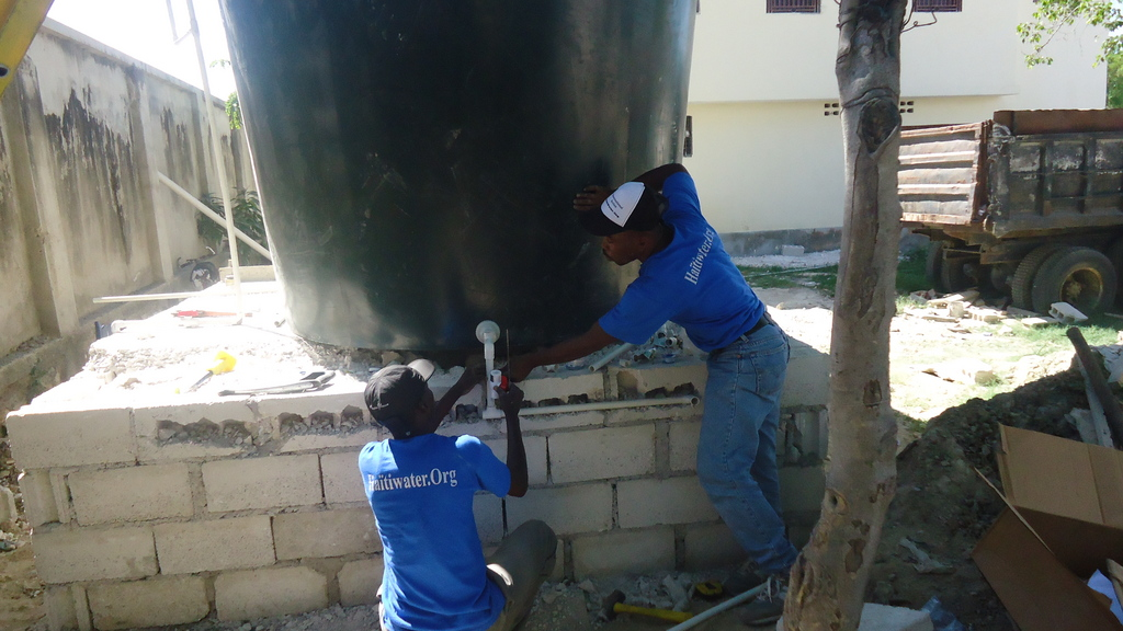 IA plumbers installing a water tank