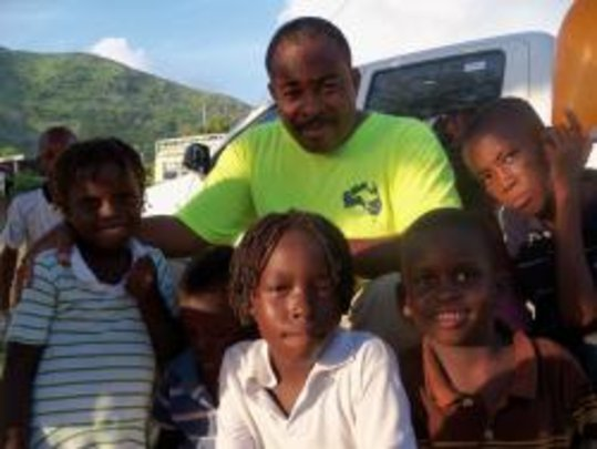 Father Dessalines helping children in the Artiboni