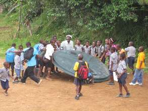 Children helping to install a 2000 gall water tank