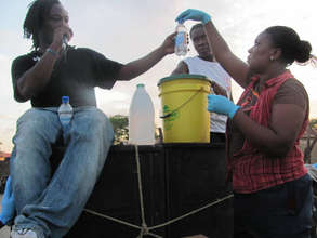 CHWs demonstrate water purification for a crowd