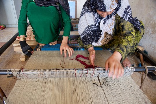 Women weaving carpets