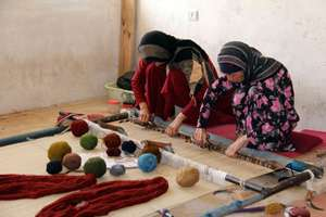 Women weaving a carpet