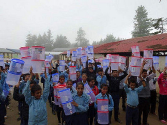Children carry home the distributed water filter
