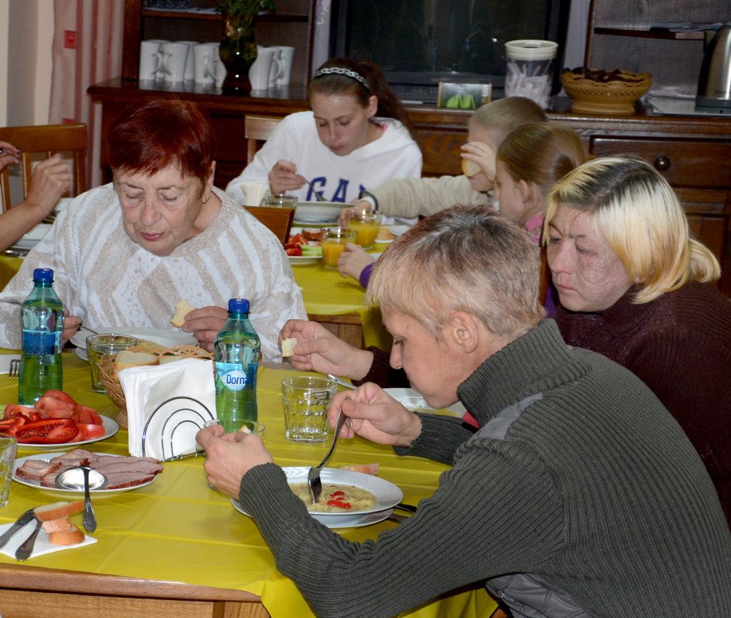 Liudmila (foreground) eats soup at Centre