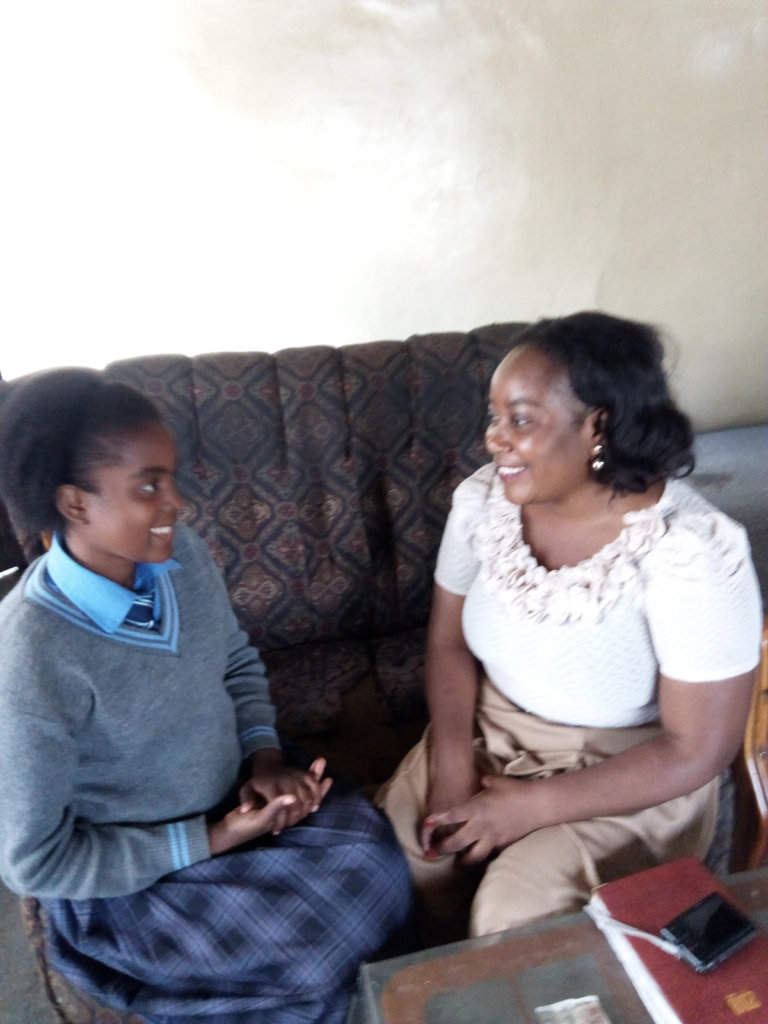 Girl discussing school with her healthcare worker