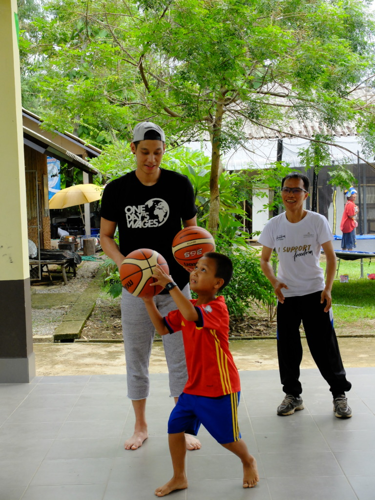 Teaching students how to shoot a basketball.