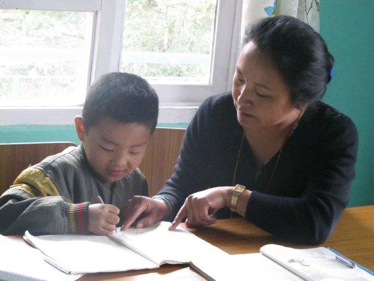 'Mother' Sukumaya helping Pawan with his homework