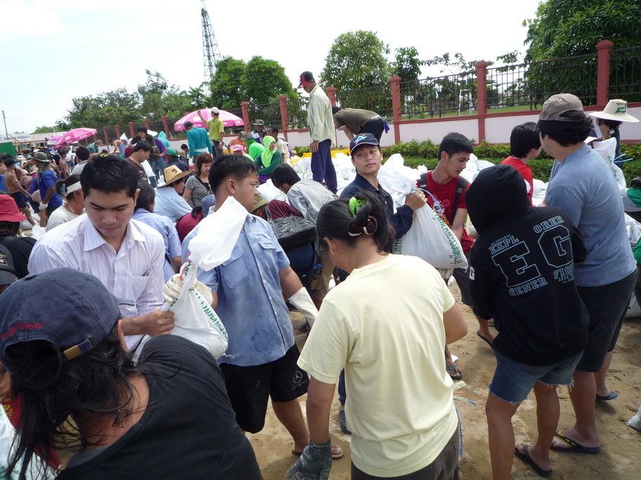 Volunteers form lines to transfer sandbags