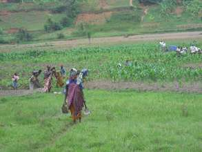 A happy Rwandan mom in front of her land