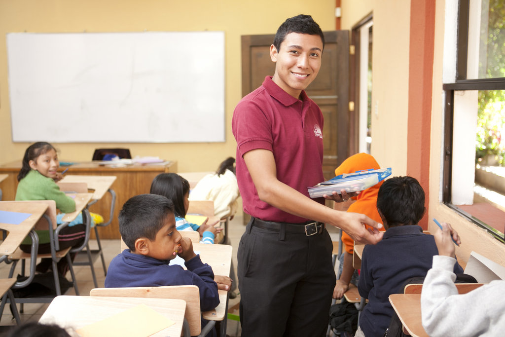 José hands out supplies to his class.