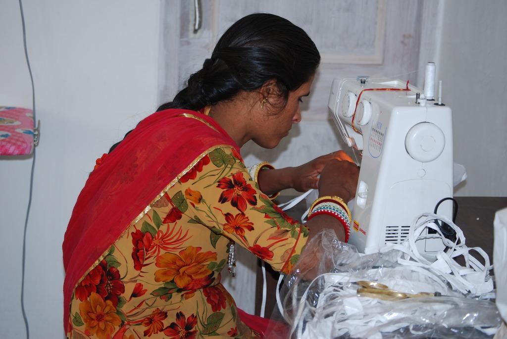 Santosh using electric sewing machine