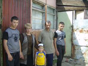 """a family in front of """"home"""" metal container"""