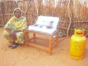 Hosna Abker sits by her new butane gas cooker.