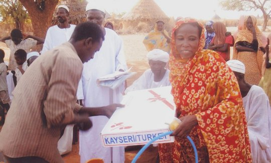 A woman receives a gas tank through microcredit.