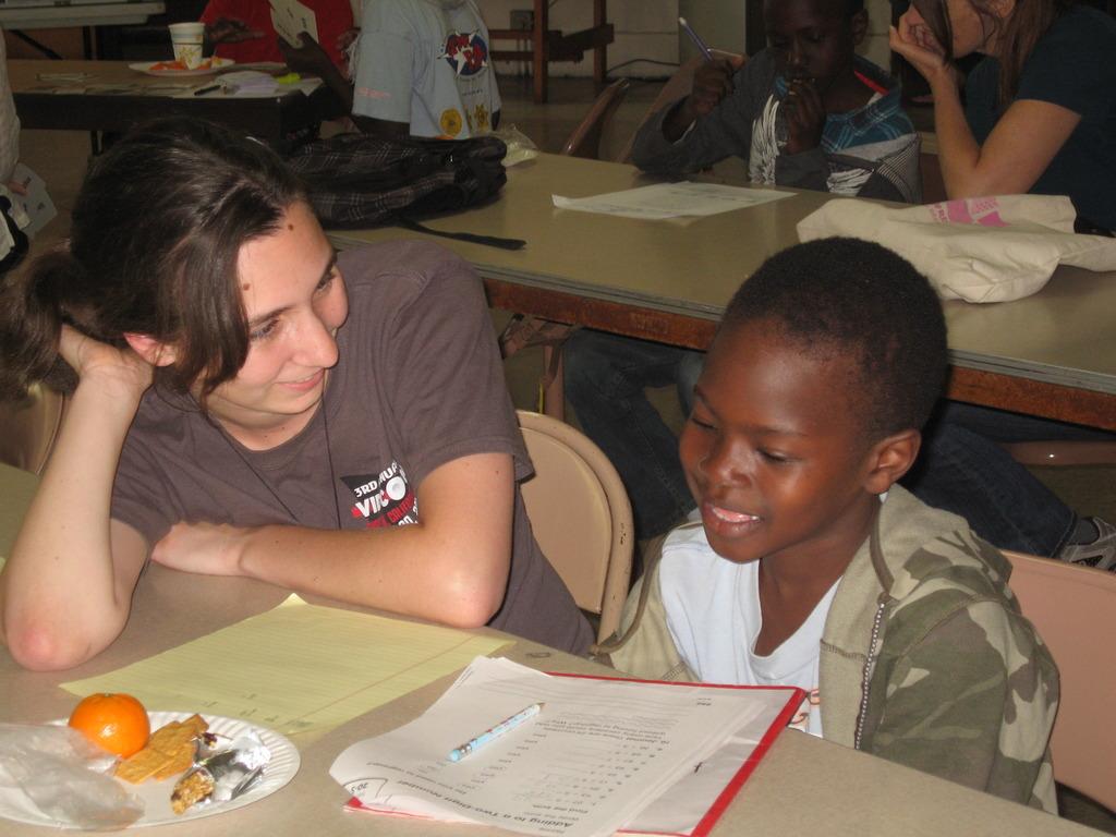 A University student tutoring a Sudanese refugee