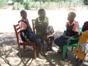 PLA Staff Susan talks to 2 beneficiaries in Lira