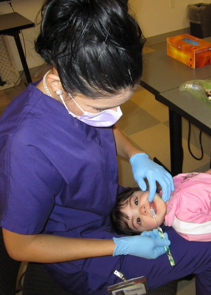 A young patient getting her teeth checked