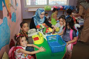 Volunteer Fatima helps facilitate imaginative play