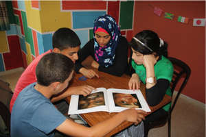 Volunteer Maysoon practices reading with students.