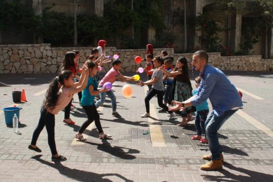 Teacher Ahmad plays balloon toss with his students
